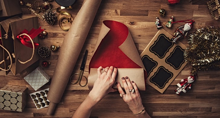 A picture of a woman's hands wrapping a christmas present.
