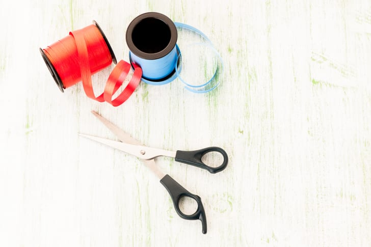 Two rolls of ribbon and a pair of scissors on a white background.