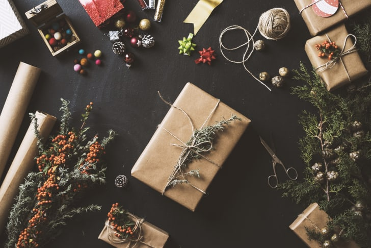 A present wrapped in plain paper and twine with a twig as an embellishment.