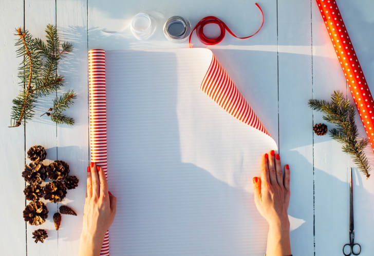 A person measuring out wrapping paper.