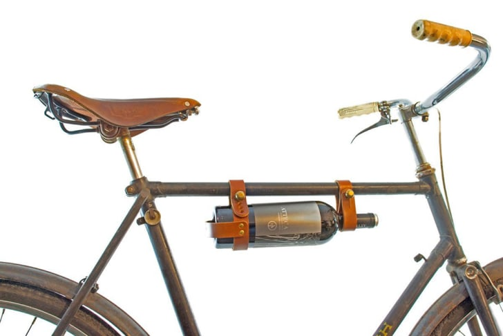 A bottle of wine strapped to the frame of a bike