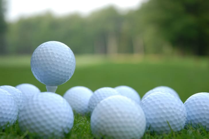 Golf balls are piled up on a golf course