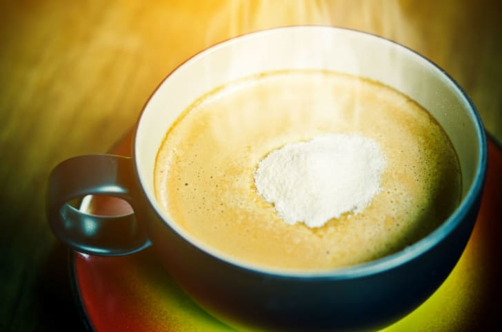 Powdered coffee creamer is shown dissolving in a cup of coffee