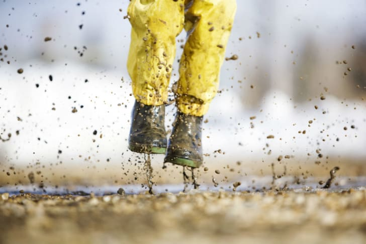 A child in rain boots stomps through the mud
