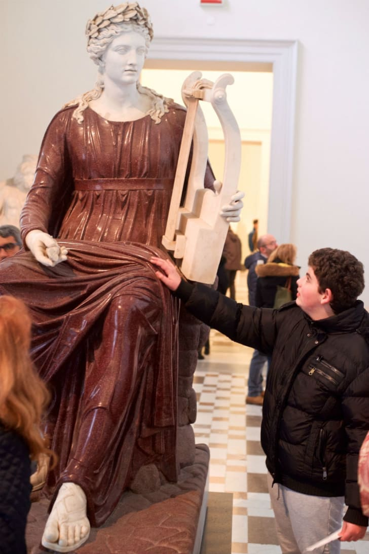 A child puts his hands on a sculpture
