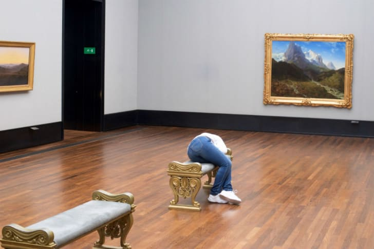 A woman sleeps on a bench in a gallery