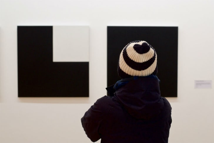 A gallery visitor in a black and white hat looks at a black and white art piece
