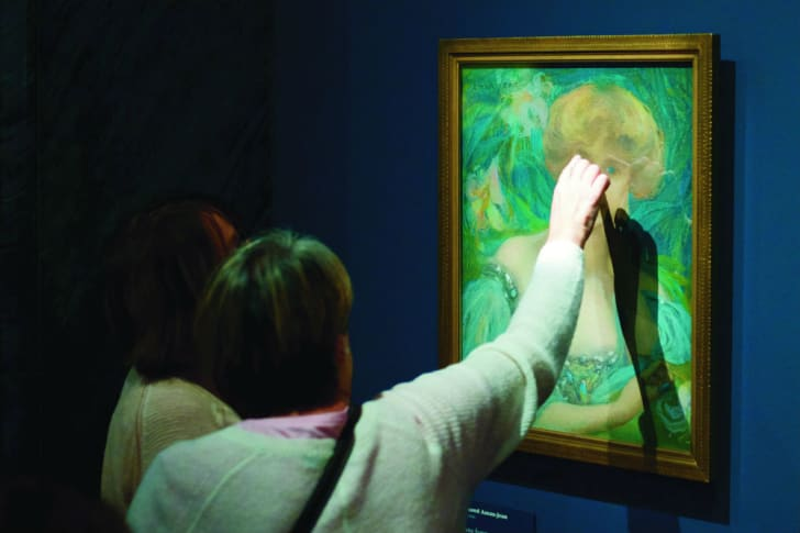 A woman touches a painting