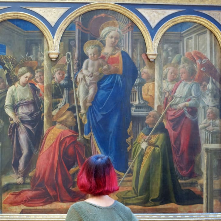 A large painting is observed by a gallery patron