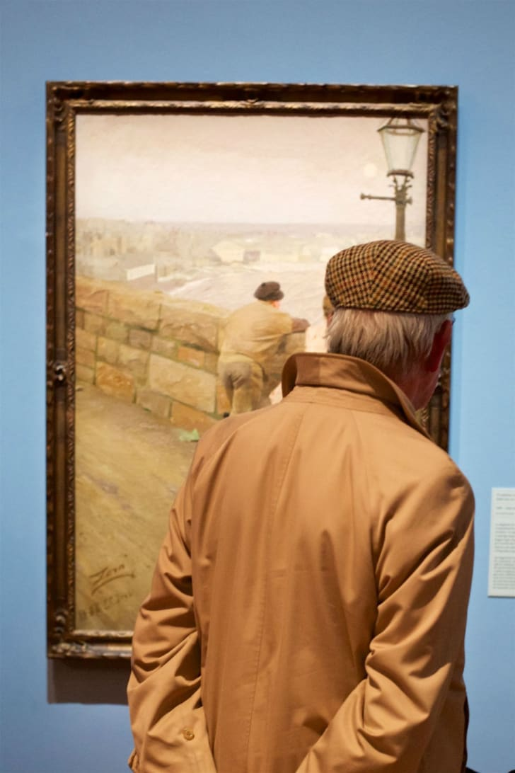 A man observes a painting in a gallery