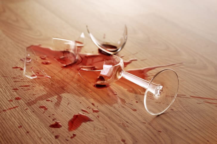 Photo of a broken red wine glass on the floor
