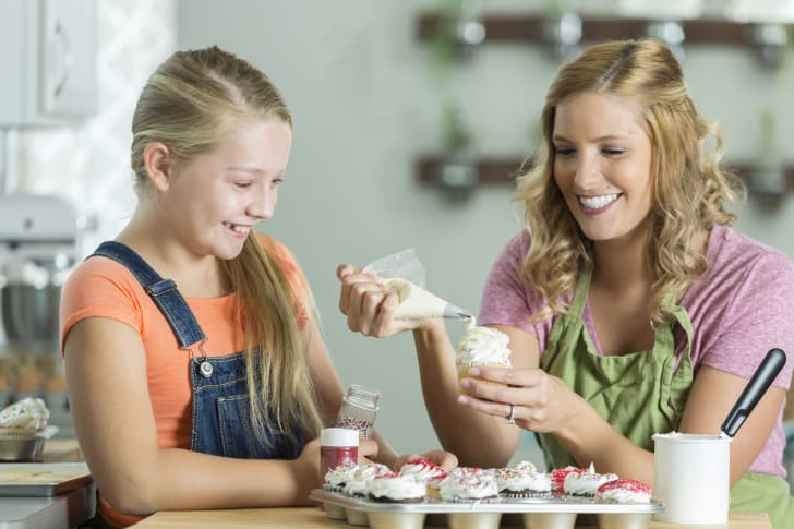 Girl and woman decorating cupcakes