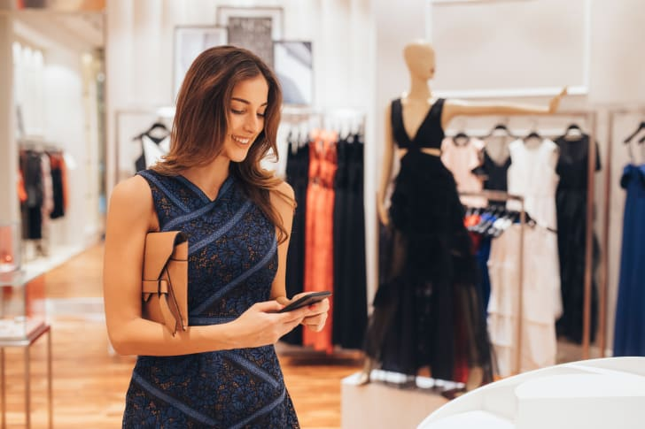 woman looking at smartphone in clothing store