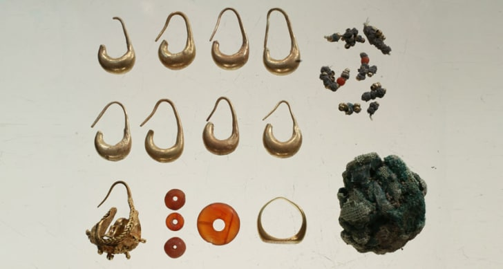 A 3100-year-old jewelry hoard, including earrings, beads, a ring, and silver jewelry wrapped in linen cloths.