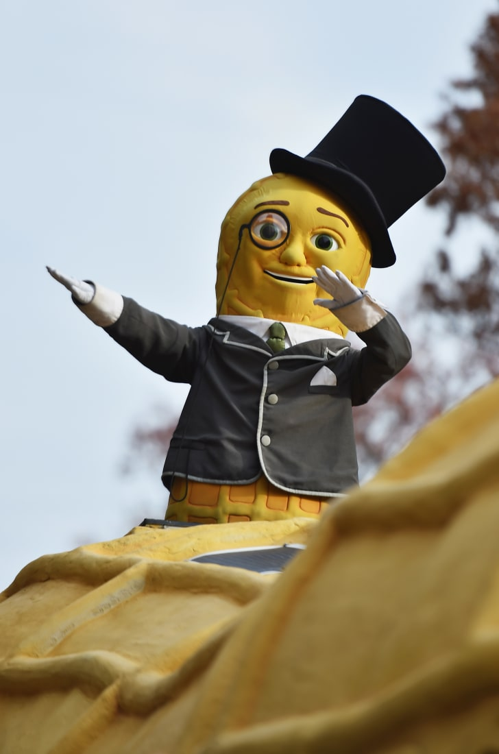 A large peanut wearing a suit and monocle is dabbing.