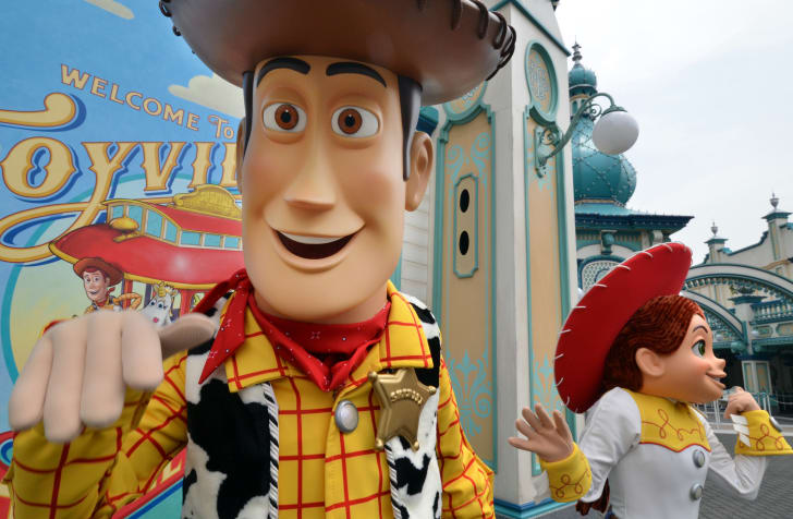 A costumed character that of Woody from Toy Story smiles at the camera while a costumed Jessie stands in the background.