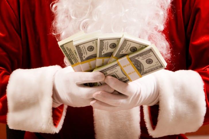 Santa holding lots of money