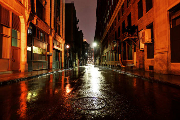 A wet street is photographed at night