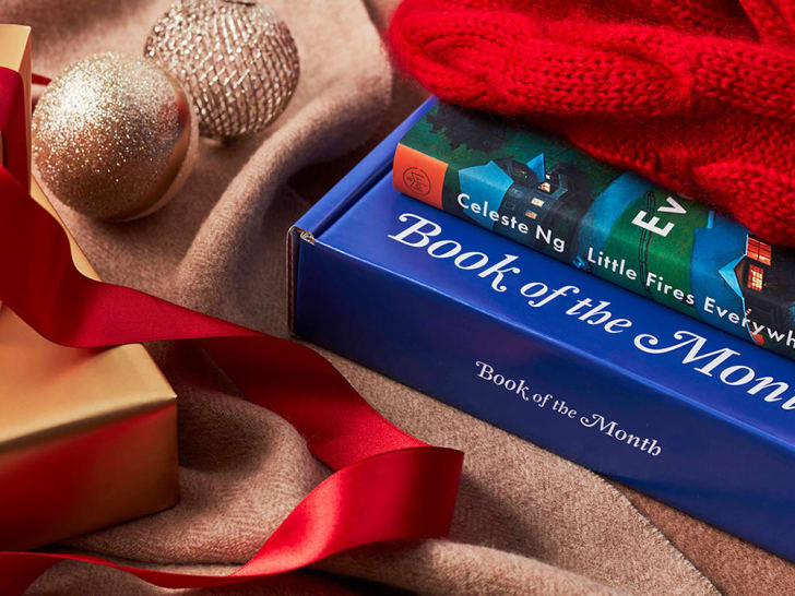 A book of the month club subscription box with gift trappings nearby