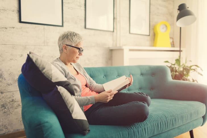 Older woman reading book on couch