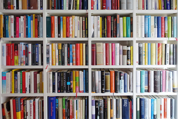 Books arranged on white shelves in a library