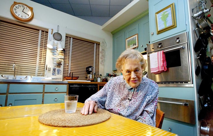 Julia Child, wearing a flowered blouse, sits in her kitchen, which has been reassembled at the Smithsonian Museum.