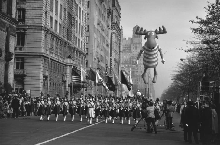 A black and white picture of an early Macy's Thanksgiving Day Parade, with a marching band in the foreground and an inflatable balloon of Bullwinkle the moose in the background.