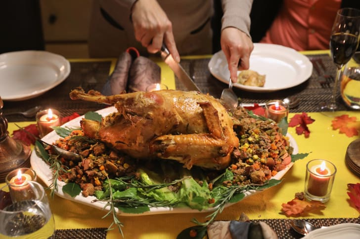 A paid of hands carving a turkey surrounded by stuffing.