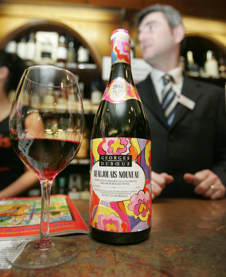 A bottle of Beaujolais Nouveau next to a glass that is one-third filled with wine. A man in a suit and tie stands in the background.