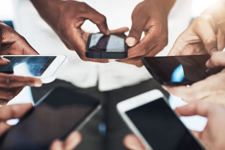 Group of hands holding smartphones.