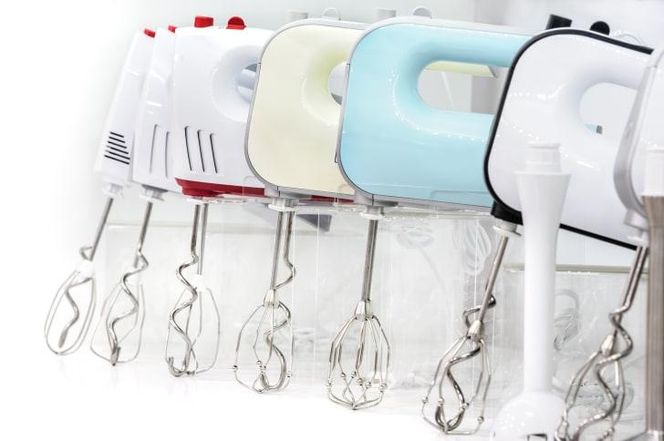 Row of hand mixer kitchen appliances.
