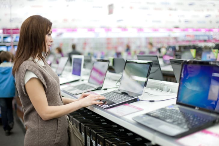 Woman testing a laptop at a store.