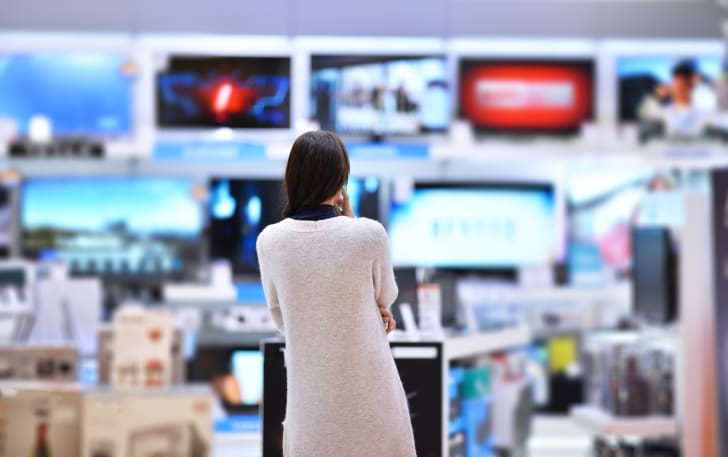 Woman shops for TVs.