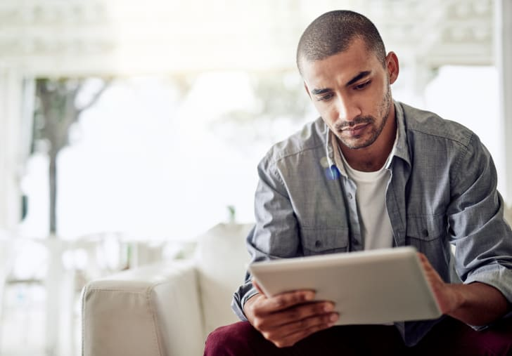 Man looks at smart tablet.