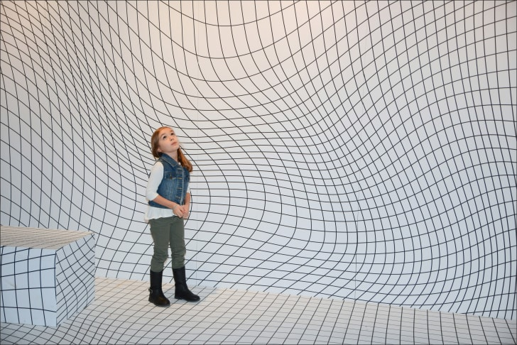 Girl standing in optical illusion room.