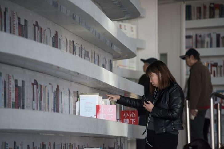 A woman looking at books at China's Tianjin Binhai Library.