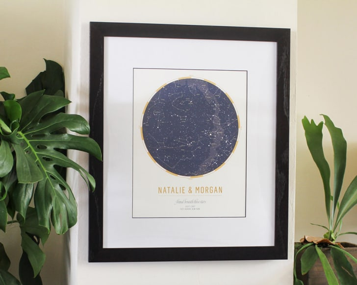 A framed poster that reads 'Natalie and Morgan' with a star chart above in dark blue