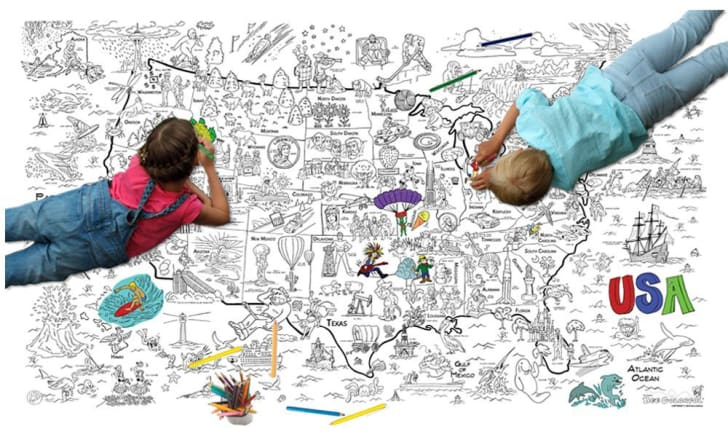 Two children lay on a giant coloring-book-style map of America