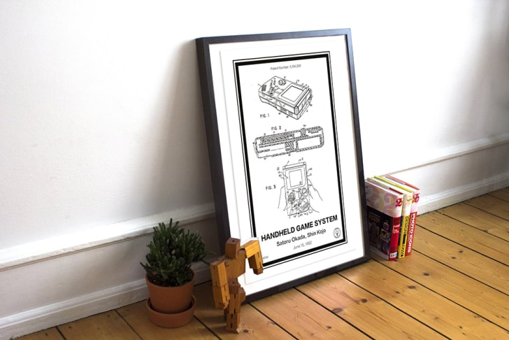A framed patent of the Nintendo Game Boy sits against a wall.
