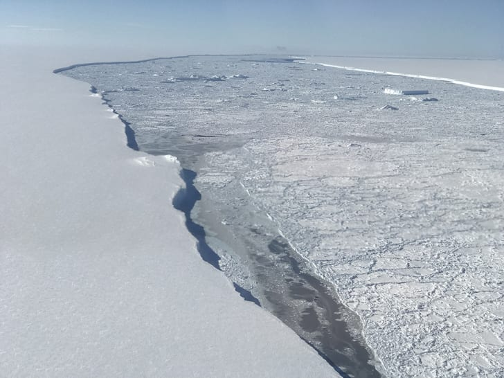 An aerial photo of an ice shelf and the iceberg it calved