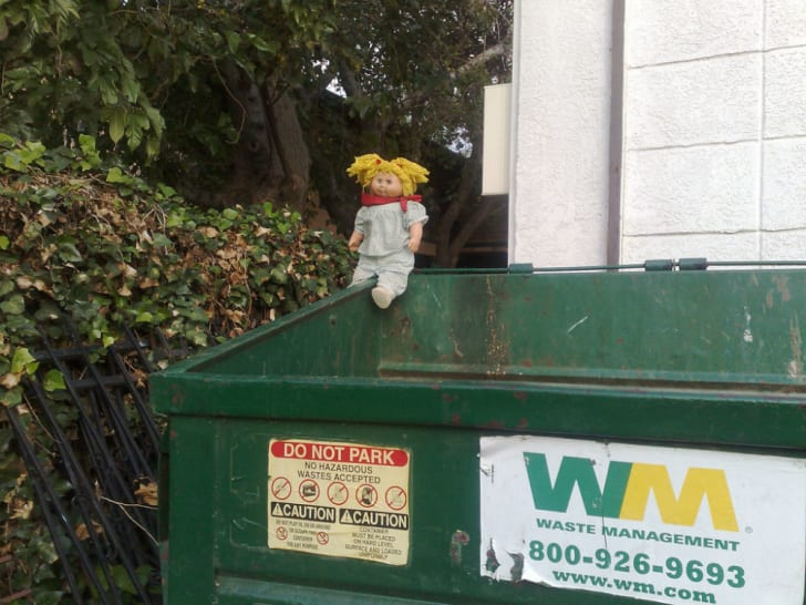 A Cabbage Patch Kid sits on top of a dumpster