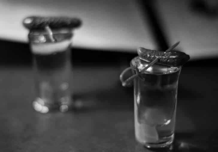 Two shot glasses topped with small pickles.