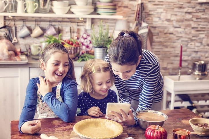 Three girls prepare a pumpkin pie according to a recipe.