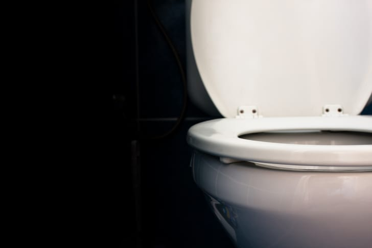 A toilet on a black background.
