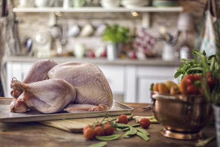 A raw turkey sitting on a cutting board.