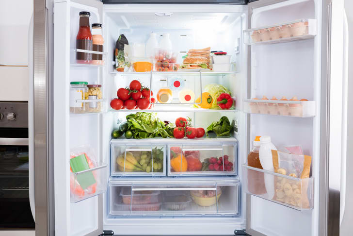 An open fridge full of fruits and vegetables.
