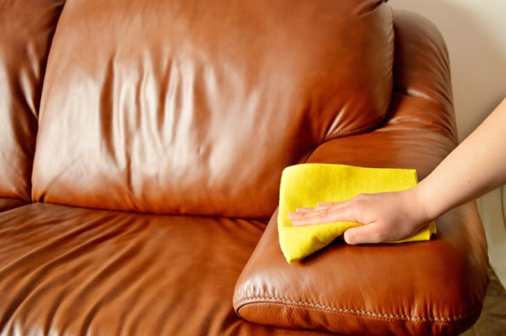Hand cleaning a leather sofa.