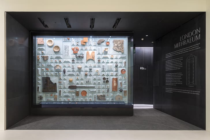 A case full of artifacts stands in the middle of a room.