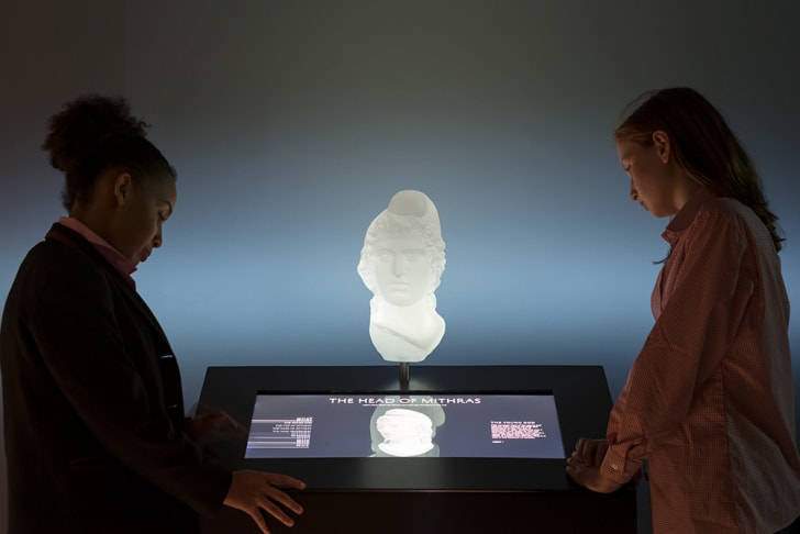 Two women look at an interactive exhibit of a bust of Mithras.