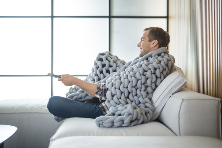 Man on couch wrapped in knit blanket.